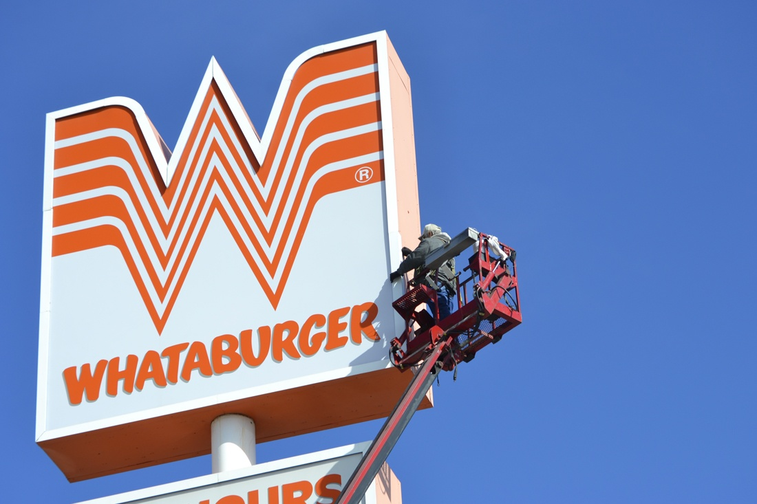 man working on whataburger pylon sign maintenance