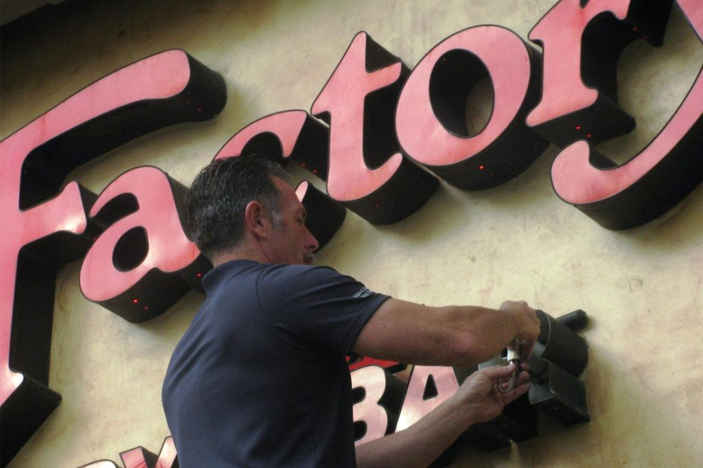 man doing maintenance on cheesecake factory channel letters