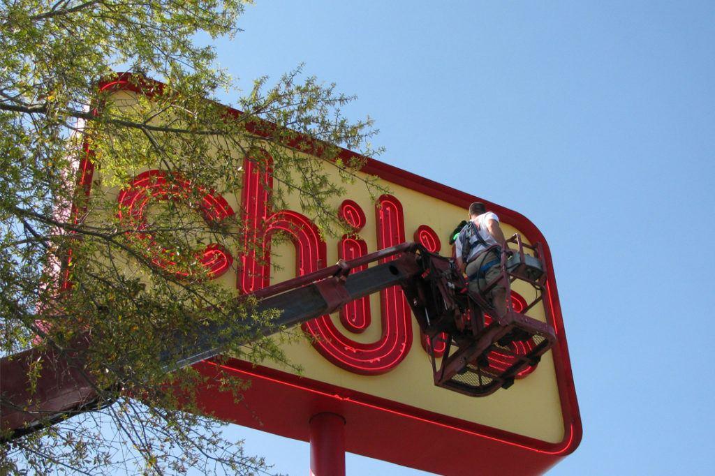 man doing maintenance on chilis pylon sign