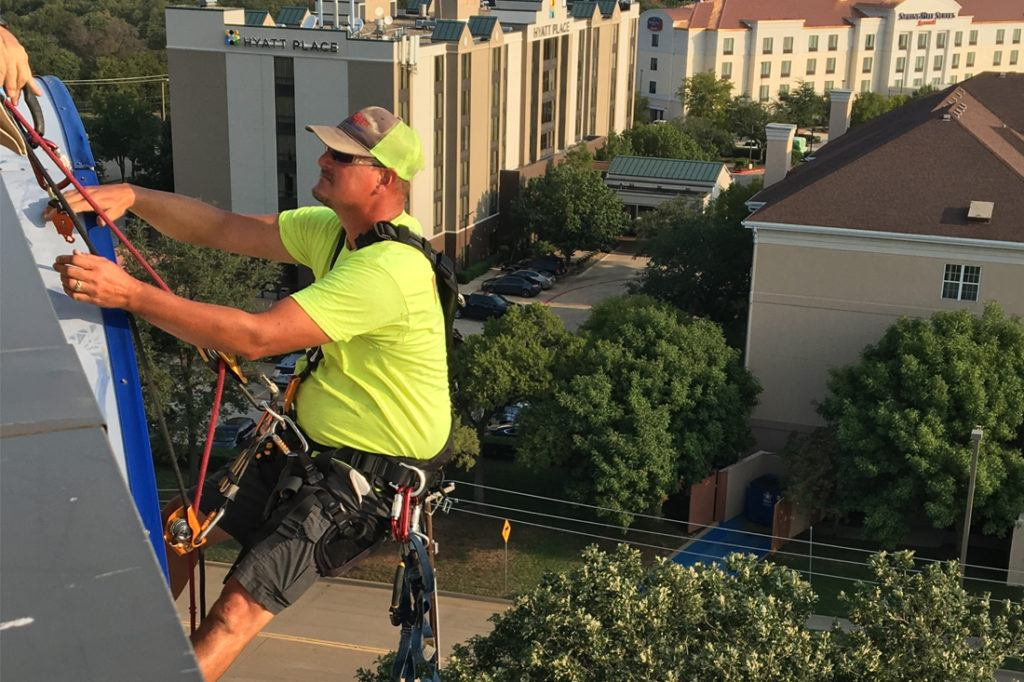 man rappelling for hilton sign maintenance