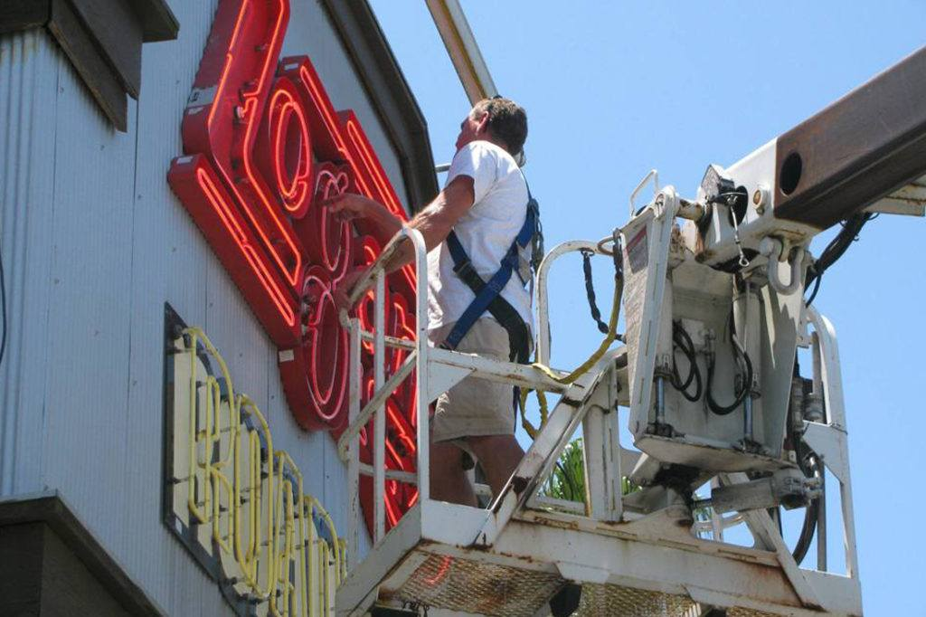 man repairing neon open face sign