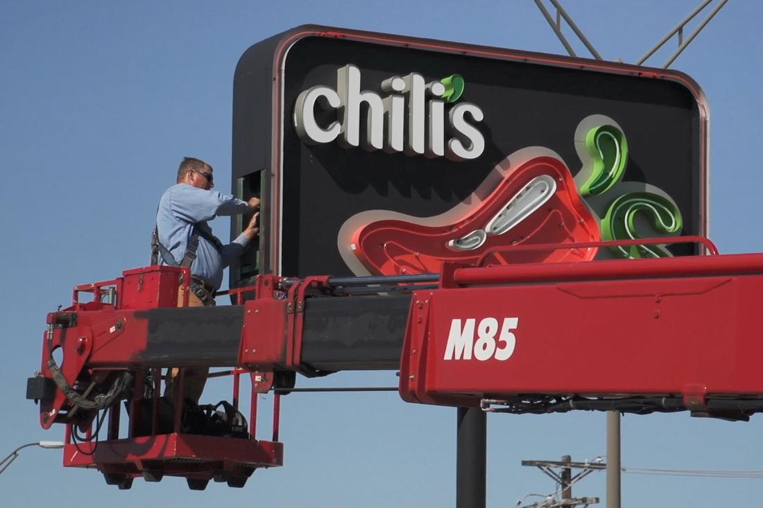 man doing maintenance on chilis pylon sign
