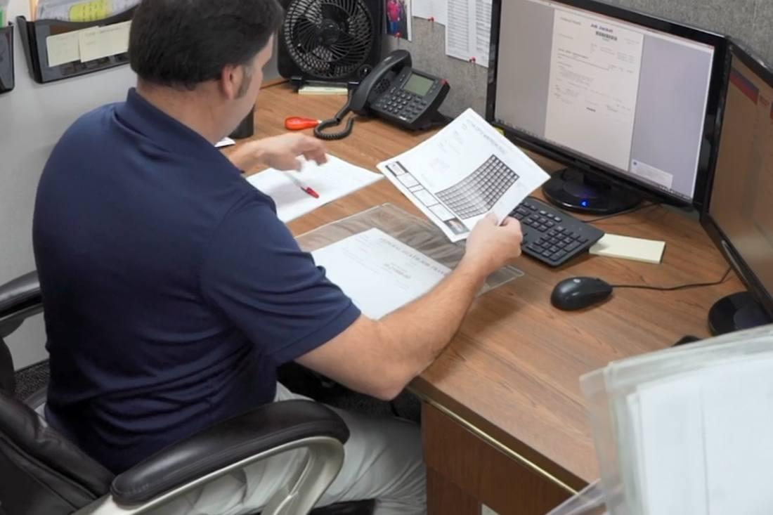 man sorting through paperwork at desk