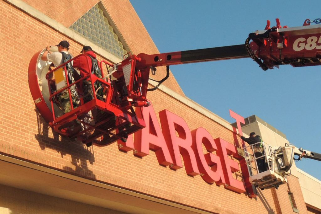 workers repairing target channel letters