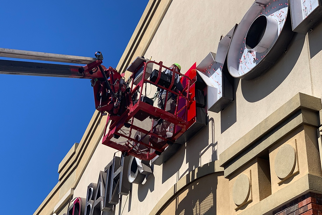 worker performing maintenance on bed bath and beyond sign